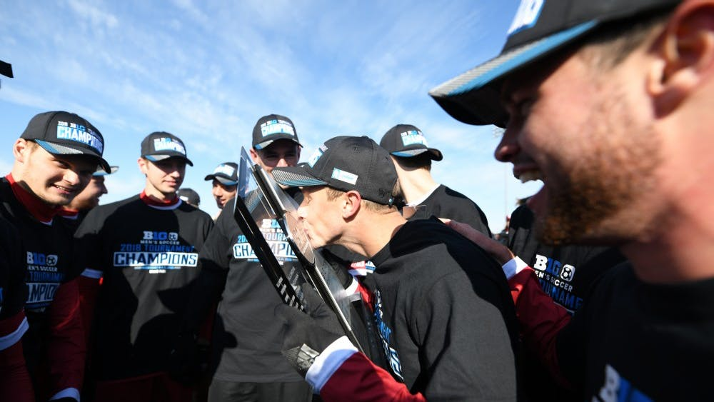 Senior defender Rece Buckmaster kisses the trophy Nov. 11 at Grand Park after IU's Big Ten Tournament championship against Michigan.