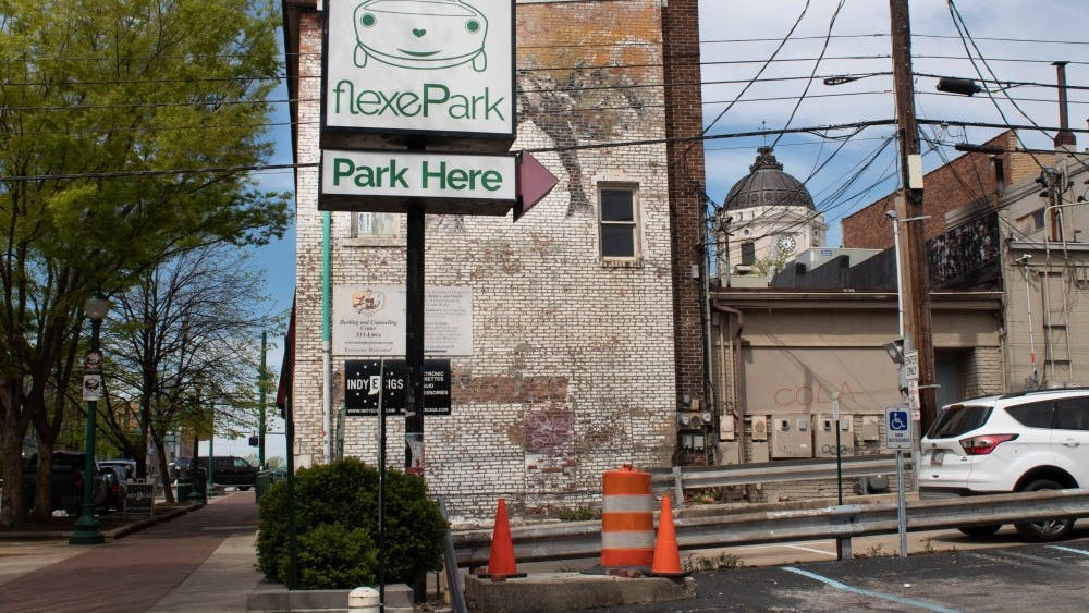 A FlexePark sign stands at the entrance of a parking lot on Kirkwood Avenue. Parking costs $6 daily, according to signs posted in the lot.