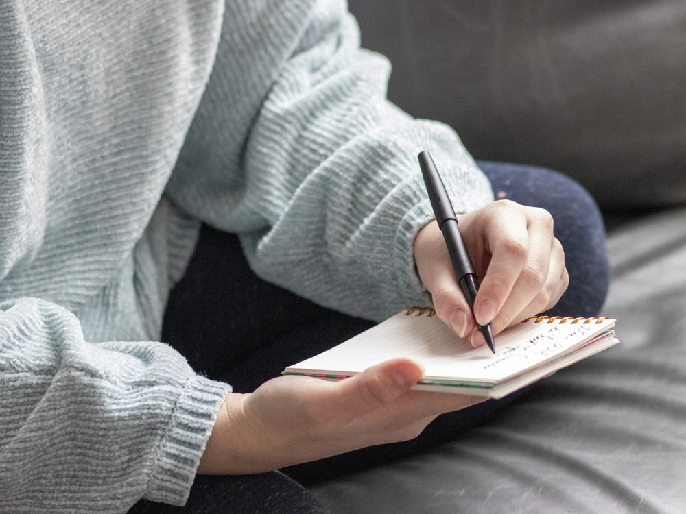 A student writes a letter Monday afternoon. Campus Cursive at IU is an organization that writes letters to people to combat loneliness.