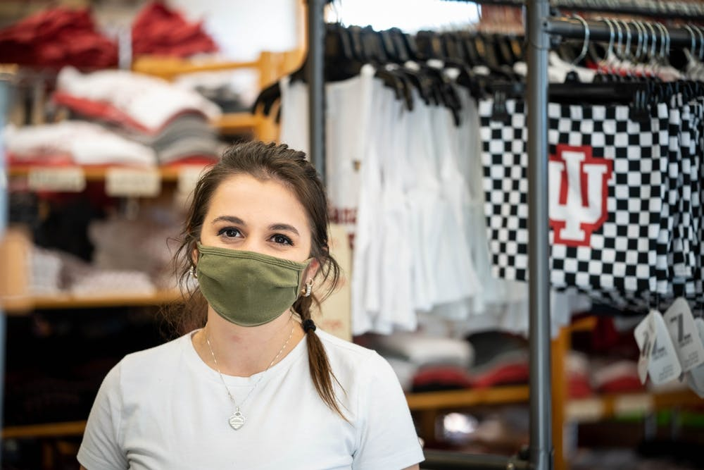 """<p>Senior Emily Axsom, a fashion design student and employee of Greetings, smiles for a photo Nov. 19 inside the store. """"If a business requires a mask I think it's important to respect that, political beliefs aside."""" said Axsom.""""If one person comes in and doesn't want to wear a mask or put it over their nose... That just makes all of the precautions we're taking not work.""""</p>"""
