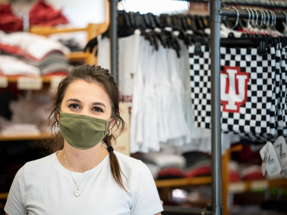 """Senior Emily Axsom, a fashion design student and employee of Greetings, smiles for a photo Nov. 19 inside the store. """"If a business requires a mask I think it's important to respect that, political beliefs aside."""" said Axsom.""""If one person comes in and doesn't want to wear a mask or put it over their nose... That just makes all of the precautions we're taking not work."""""""