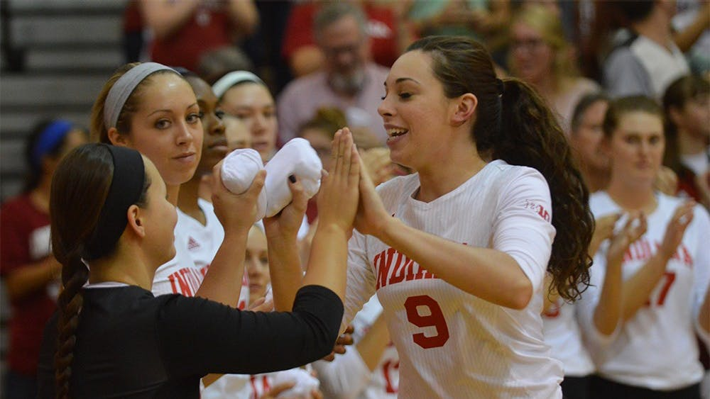 Megan Tallman gives high fives to other teammates as they are announced before the game against Purdue on Oct. 7. The Hoosiers lost 0-3