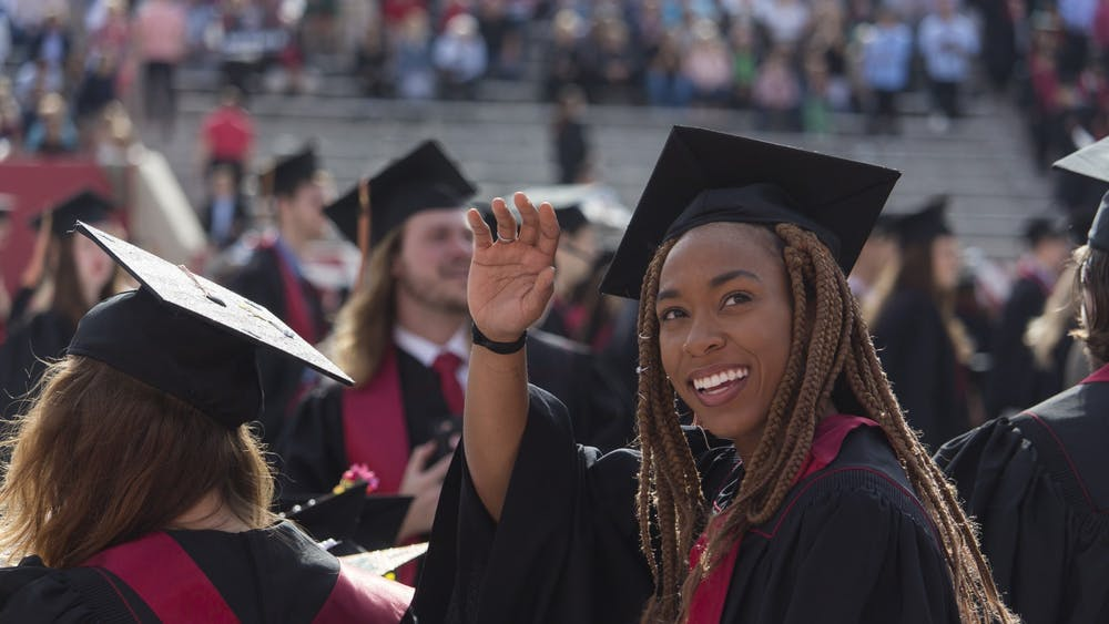 A former IU student waves to the audience during the 2018 undergraduate commencement ceremony May 5, 2018, in Memorial Stadium.