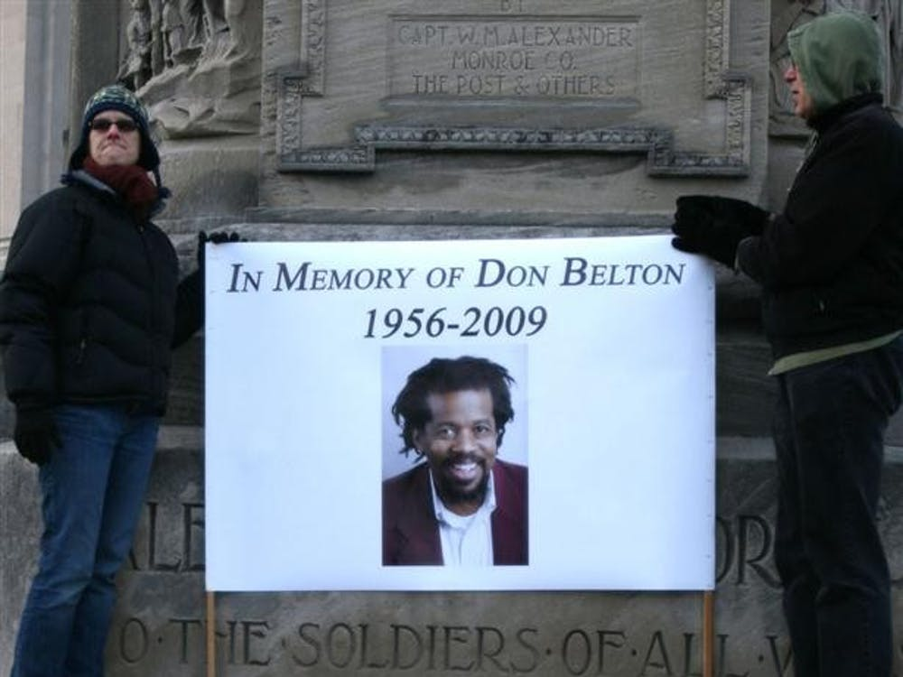 A sign is held on Bloomington's Courthouse Square during a memorial for assistant professor Don Belton, New Year's Day.  Belton, 54, was killed in his home by Michael James Griffin, 26, on Dec. 27, 2009.