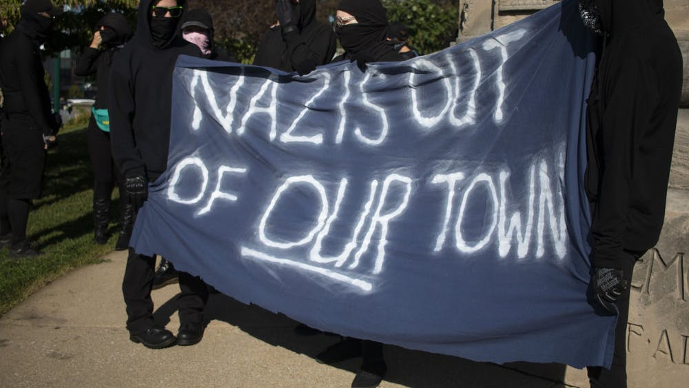 "Members of antifa hold a large banner stating, ""Nazis out of our town,"" Aug. 24, 2019, outside the Monroe County Courthouse in Bloomington. The group, along with members of No Space for Hate, marched to the Bloomington Community Farmers' Market to protest Schooner Creek Farm, which is allegedly run by people who have ties to the white nationalist group American Identity Movement."