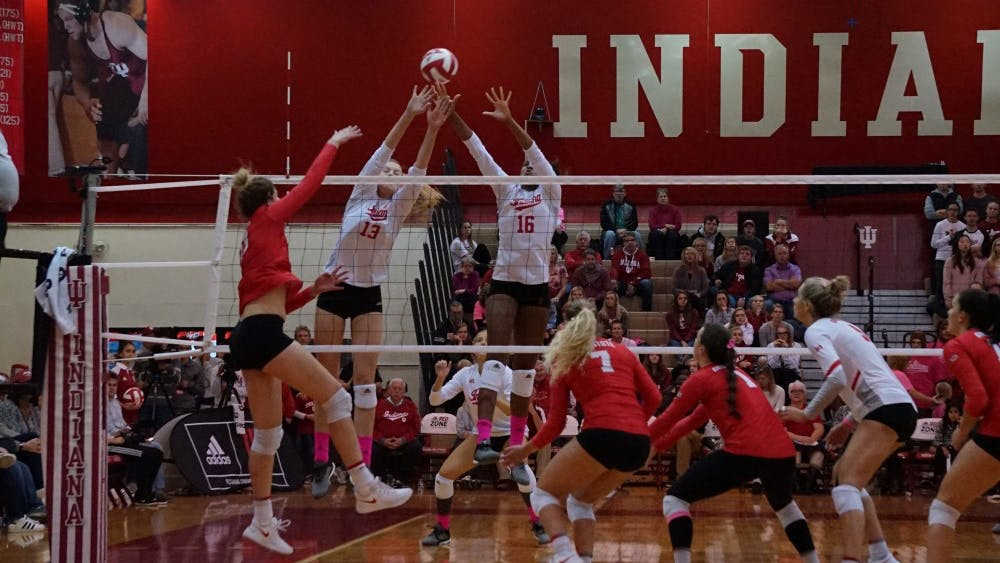 Freshman middle blocker Lexi Johnson and junior blocker Deyshia Lofton jump up to block the ball against an Ohio State attacker Oct. 19 in University Gym. IU will face Penn State and Rutgers this weekend.