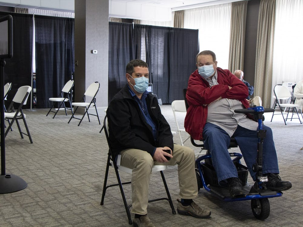 Two Bloomington residents sit in the waiting area after receiving doses of the Moderna COVID-19 vaccine Feb. 24 at the Monroe Convention Center. People are required to remain in a waiting area  for 15 minutes after receiving the vaccine to make sure they don't have any side effects.