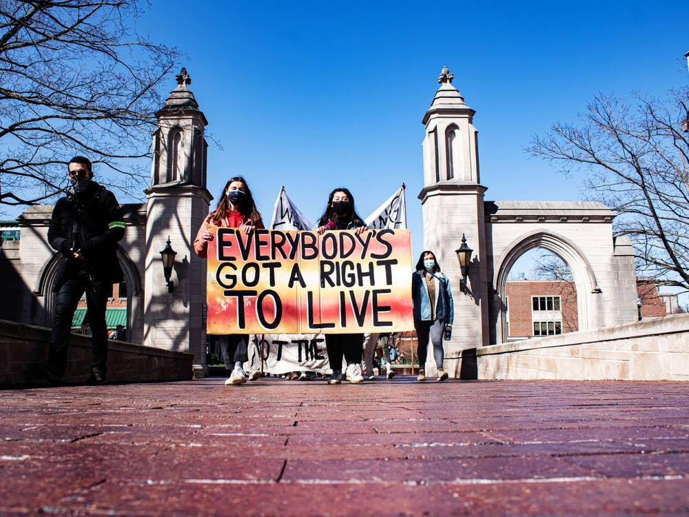 """Dozens of protesters march into campus Saturday afternoon for the """"March to End the Madness.'' The group walked to IU's tailgate fields where they hoped to gather attention from the ongoing NCAA men's basketball tournament games."""