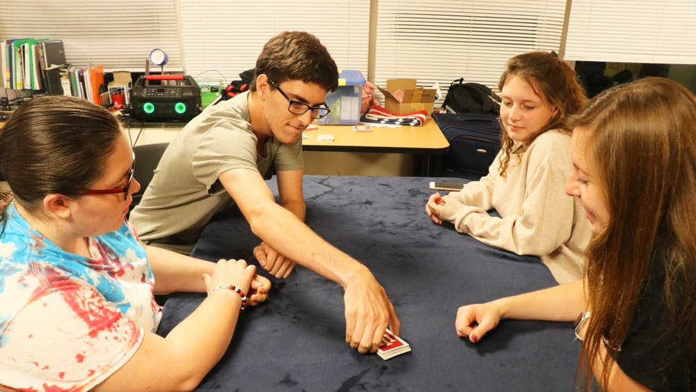 Kenzie Burgess, Reese Myers, Kacie Scales and Jada Collins play a game of euchre on Sept. 17, 2019, in Teter Quad.