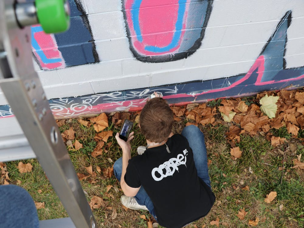 Sophomore Trenton Musch works on a mural Nov. 20 outside of The Warehouse in Bloomington. The face in this mural is based off of Shun Lin, his neighbor and friend.