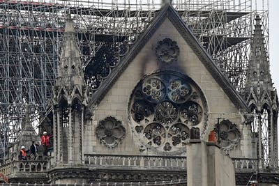 Inspectors are seen April 16 on the roof of the landmark Notre Dame Cathedral in central Paris the day after a fire ripped through its main roof.