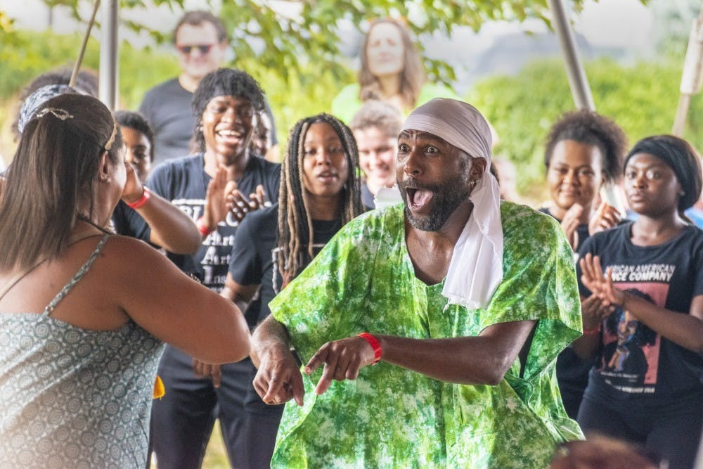<p>Stafford Berry, African American Dance Company director, dances with someone from the audience Sept. 28, 2019, at the Lotus World Music and Arts Festival in Bloomington. The annual Lotus Festival will take place virtually this weekend, with the exception of one live, socially distanced concert at 1 p.m. Saturday at Switchyard Park.</p>