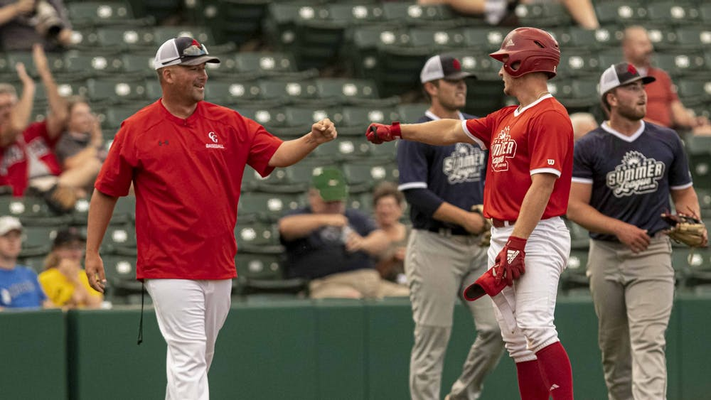 Junior Cole Barr gives red team third base coach Kevin Conder a fist bump after hitting a three-run triple July 16 at Victory Field. Barr's triple led the red team to overpower the blue team in a 4-2 victory.