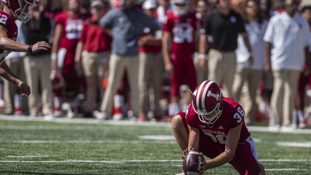 Redshirt sophomore Drew Conrad holds the ball for an extra-point attempt after a touchdown attempt during IU's game against Ball State Sept. 15 at Memorial Stadium.