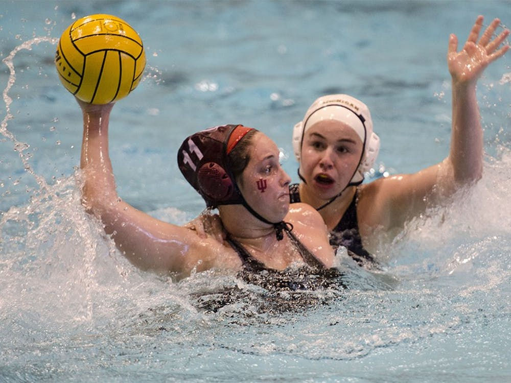 IU defender Amanda Redfern prepares to shoot the ball, away from an attacking opponent, during the Fluid Four tournament between IU and Michigan Feb. 23, 2014 at the Counsilman-Billingsley Aquatic Center. Hoosiers beat the Wolverines 12-5.