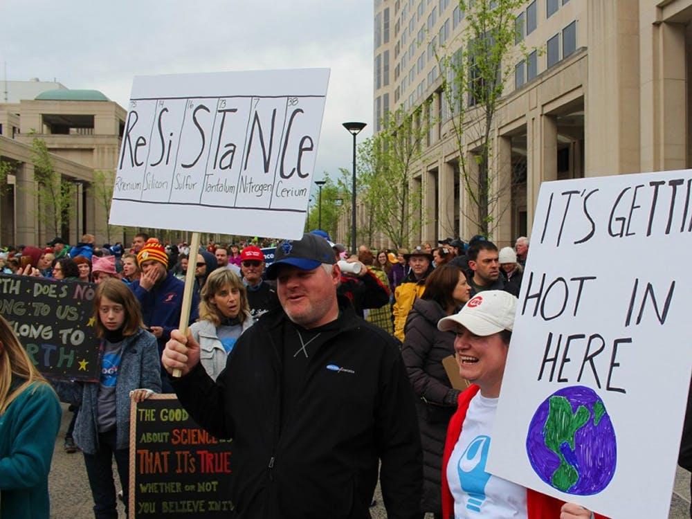 Carey and Keith Gaskill, Indianapolis residents, hold up their signs before the March for Science begins on Saturday morning. Keith is a local geochemist.