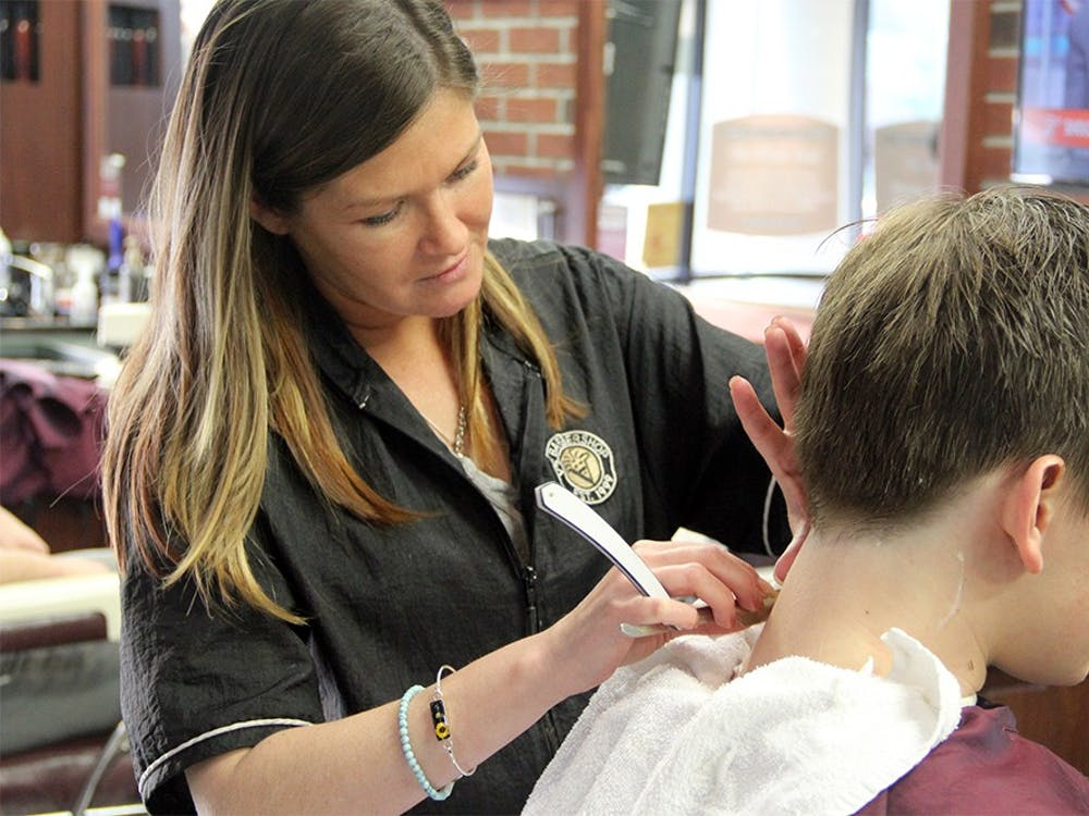 Lindsey Austin uses a straight edge razor to shave a customer's neck Monday V's Barbershop. In Indiana, only licensed barbers are legally allowed to use these tools on customers.