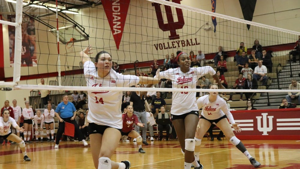 Senior right side hitter Elizabeth Asdell and middle blocker Deyshia Lofton prepare to block Oct. 31 during IU's game against Michigan in University Gym. IU defeated Michigan, 3-1.