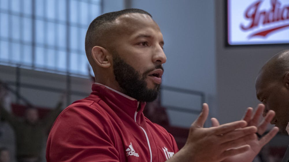 """IU wrestling coach Angel Escobedo cheers on IU on Feb. 2 at Wilkinson Hall. With the remainder of the wrestling season canceled, Escobedo has gone from coaching players to coordinating his own """"daddy day care."""""""