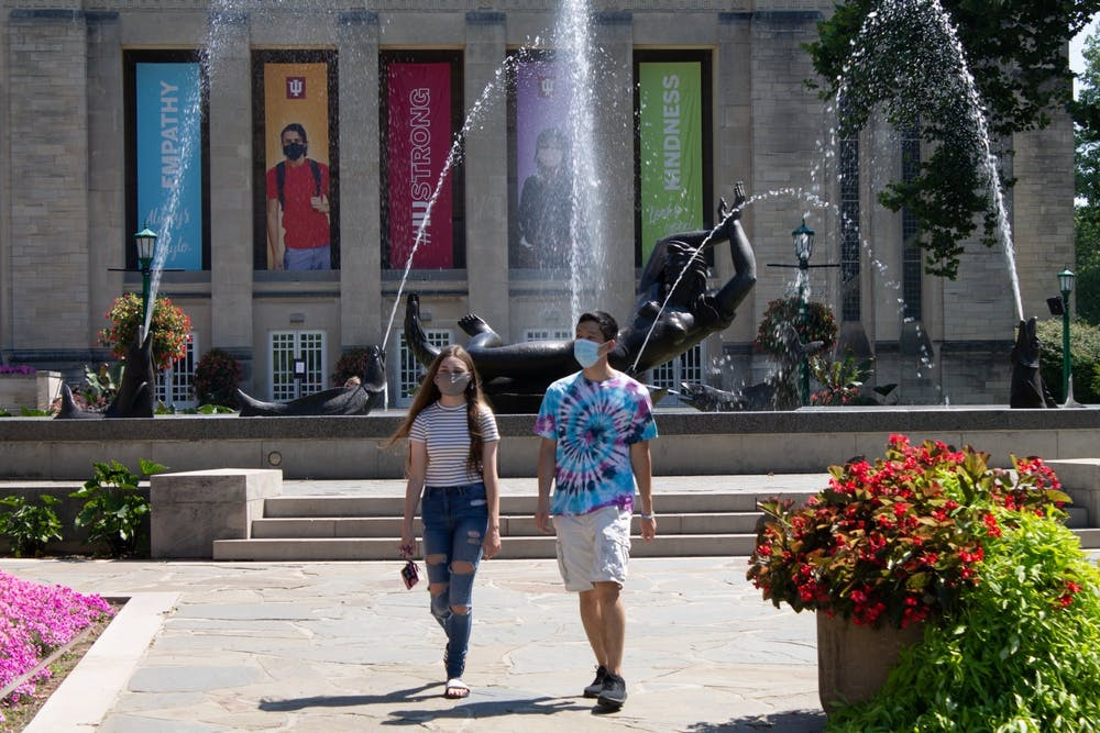 <p>Freshmen Carter Tran and Allison Being walk Aug. 24 near Showalter Fountain. Most masking and physical distancing requirements are lifted for the fall 2021 semester, according to IU.</p>