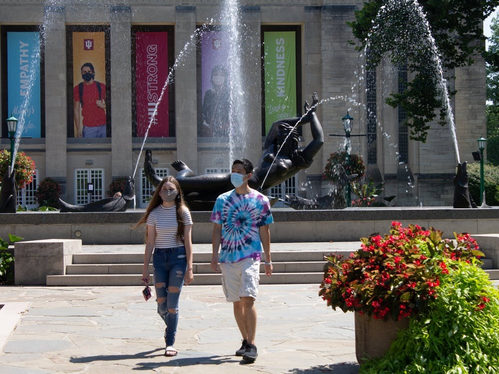 Freshmen Carter Tran and Allison Being walk Aug. 24 near Showalter Fountain. Most masking and physical distancing requirements are lifted for the fall 2021 semester, according to IU.