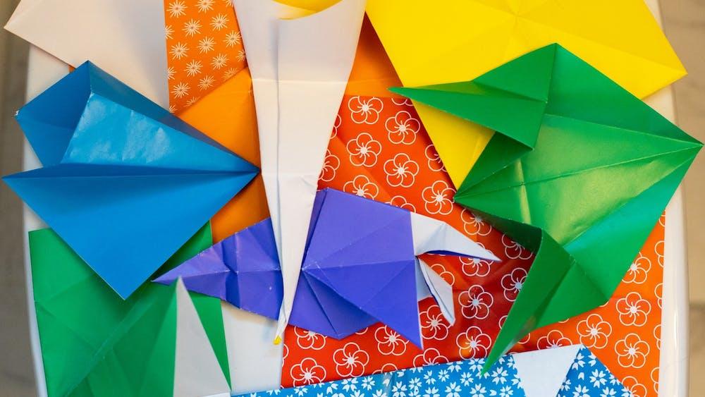 A pile of failed origami pieces lie on the bathroom floor.
