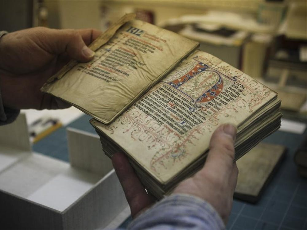 Head of Conservation James Canary shows a 15th century book he will repair at the Lilly Library .