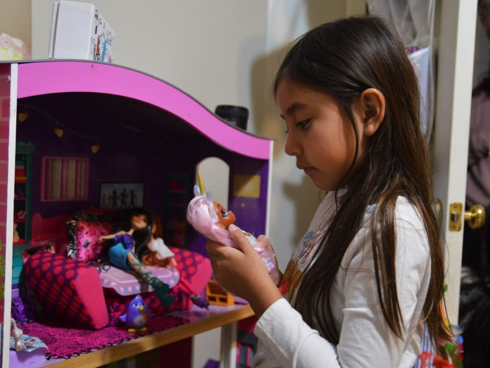 """Emi, the youngest of the Carmona family, tends to the hair of one of her toys. She had to leave her old toys behind in San Cristobal, Venezuela, one part of the """"hard stuff"""" she says each family member had to face."""