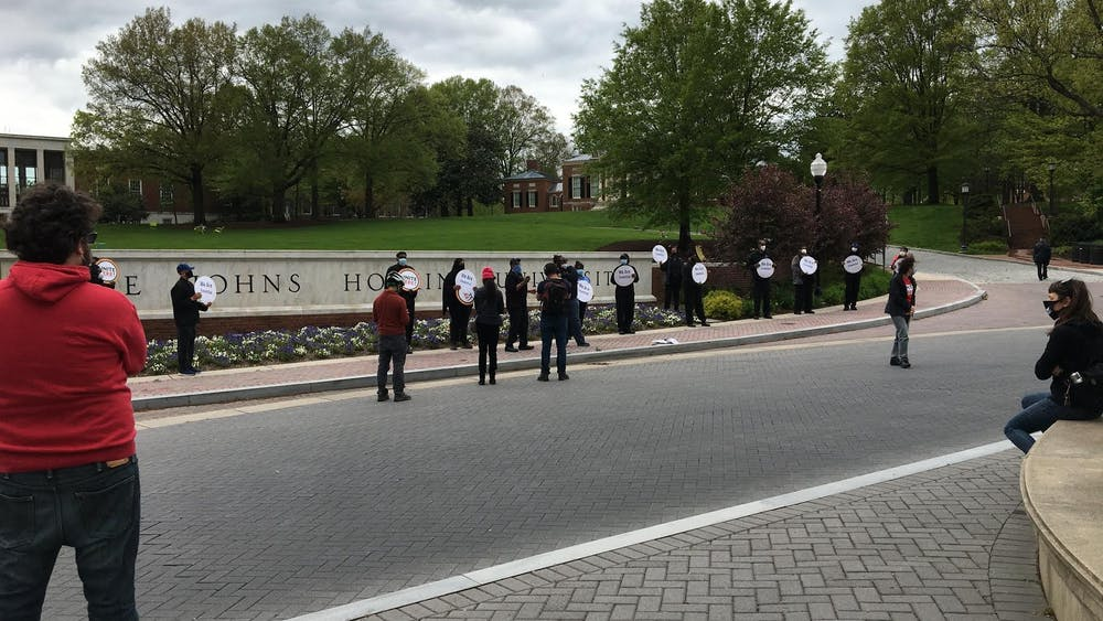 COURTESY OF KATIE TAM Protesters object University decision to suspend payments for its furloughed workers.