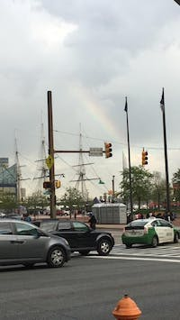 COURTESY OF RENEE SCAVONE A streetside view of shipmasts under a rainbow at the Inner Harbor.