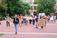 COURTESY OF ALIREZA GHASEMI Hopkins community members protest the JHU-ICE contract in September.