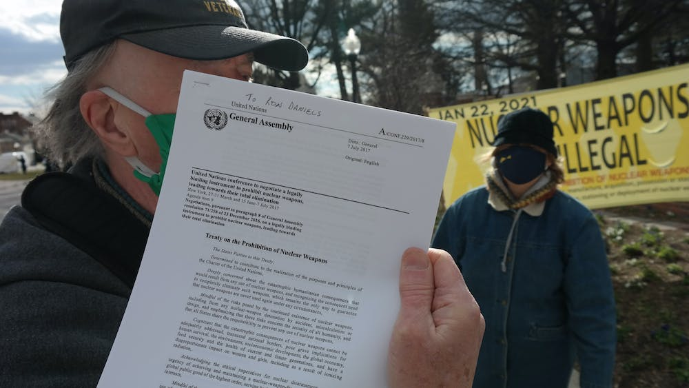 COURTESY OF CHRIS H. PARK A protester holds up the text of the TPNW that he plans to tape on the door of the Nichols House where University President Ronald J. Daniels resides.