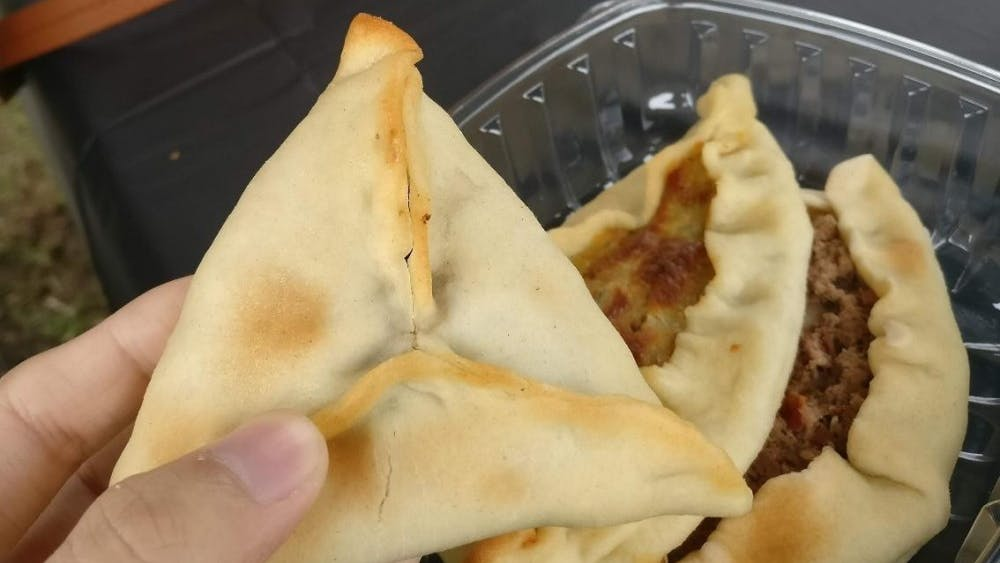 COURTESY OF JESSE WU Trying fatayer, a Middle Eastern meat/cheese/spinach pie, at the festival.