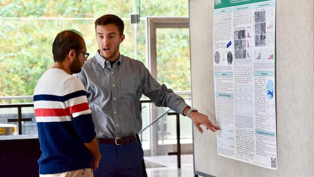COURTESY OF THE INSTITUTE FOR NANOBIOTECHNOLOGY Christopher Domalewski, who won Fan Favorite, explains his project to Ahmed Shabana, a postdoctoral fellow.