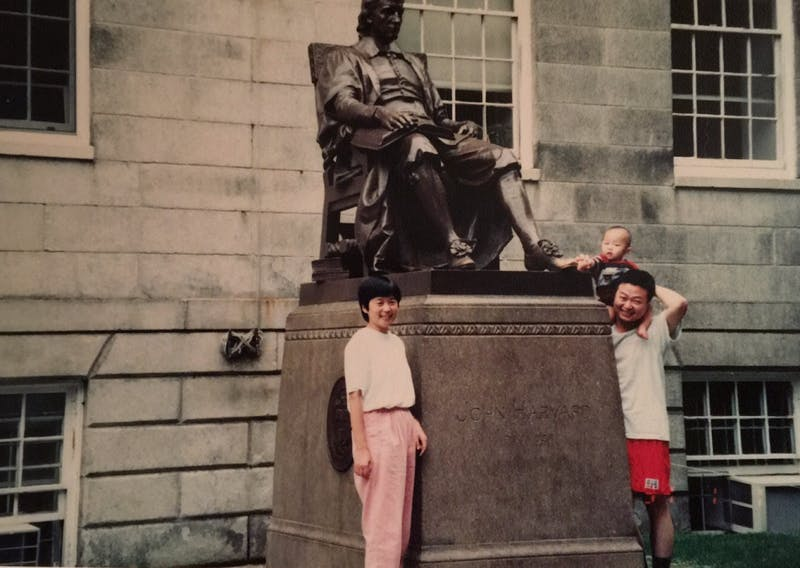 COURTESY OF ROLLIN HU Hu, pictured top right, visits John Harvard's statue with his parents.