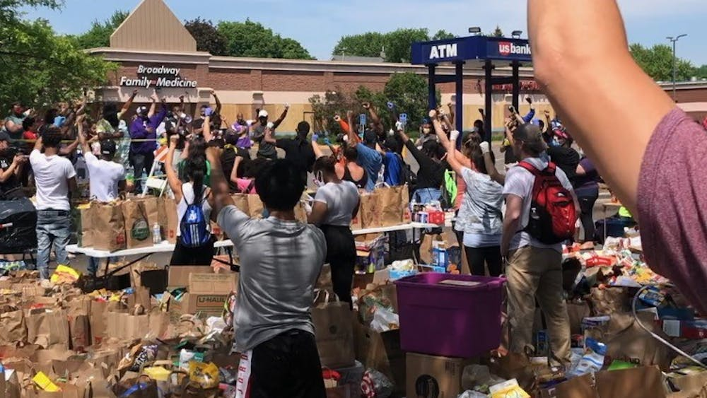 COURTESY OF ELISE MOORE At a Minneapolis food bank, people placed their right fists over their hearts, raised their left fists in the air and held their breath for 10 seconds in memory of George Floyd.