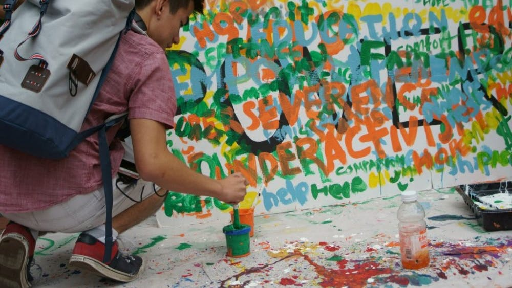 COURTESY OF NANCY WANG Students painted words associated with poverty outside Levering.