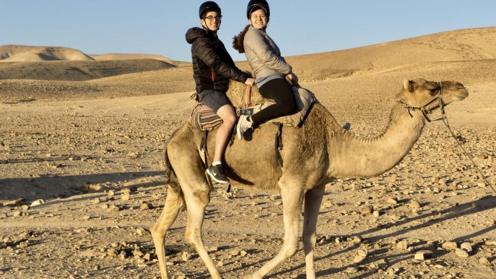 Courtesy of Rudy Malcom Malcom and sophomore Sabrina Sussman on a camel near the Kfar Hanokdim oasis.