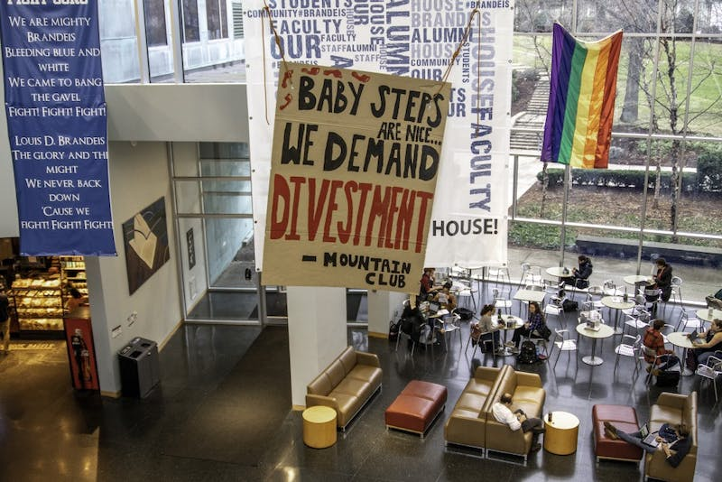 The Brandeis Mountain Club hung a banner in the Shapiro Campus Center Atrium on Monday to protest the Board of Trustees' decision on fossil fuel divestment.