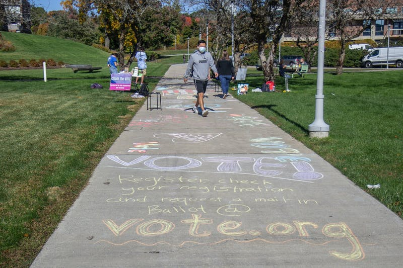 Students added voting-related contributions to a sidewalk mural for the Chalk the Vote Event on Wednesday.