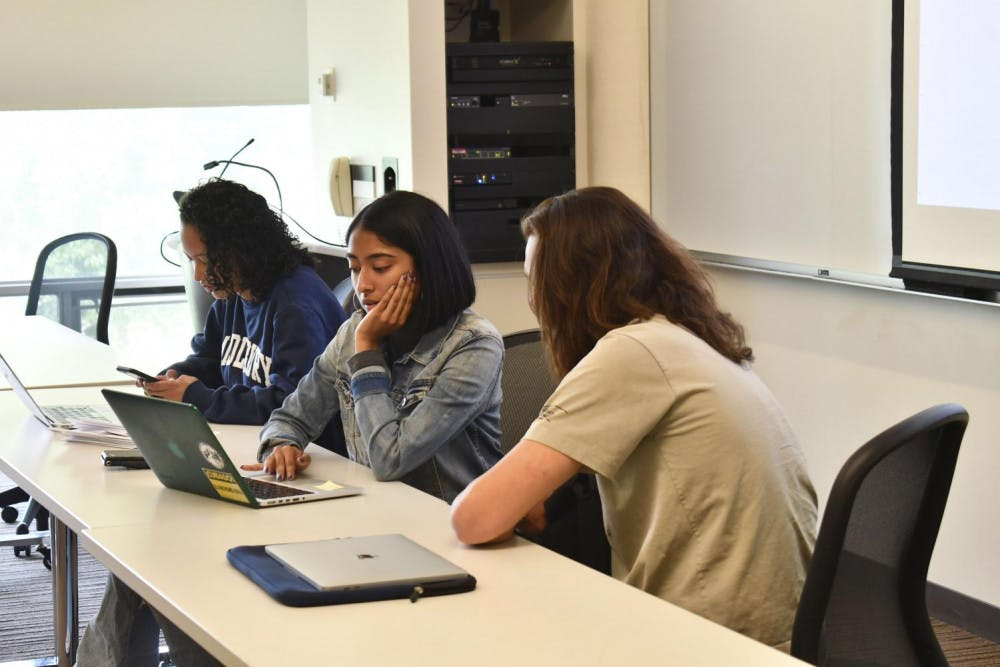 """<span class=""""photocreditinline""""><a href=""""https://middleburycampus.com/43248/uncategorized/max-padilla/"""">MAX PADILLA</a></span><br />Vijayakumar consults with a committee director during a student government meeting last Sunday."""
