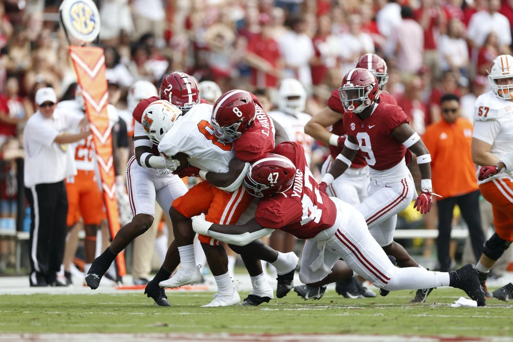 Mercer running back Brandon Marshall (#8) rushes forward while being pulled down by three Alabama players. Photo by CrimsonTidePhotos.