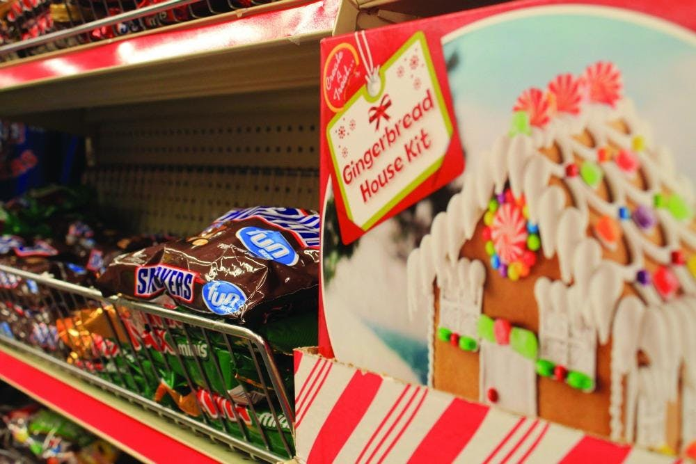 Christmas gingerbread house set on shelf directly by Halloween candy.