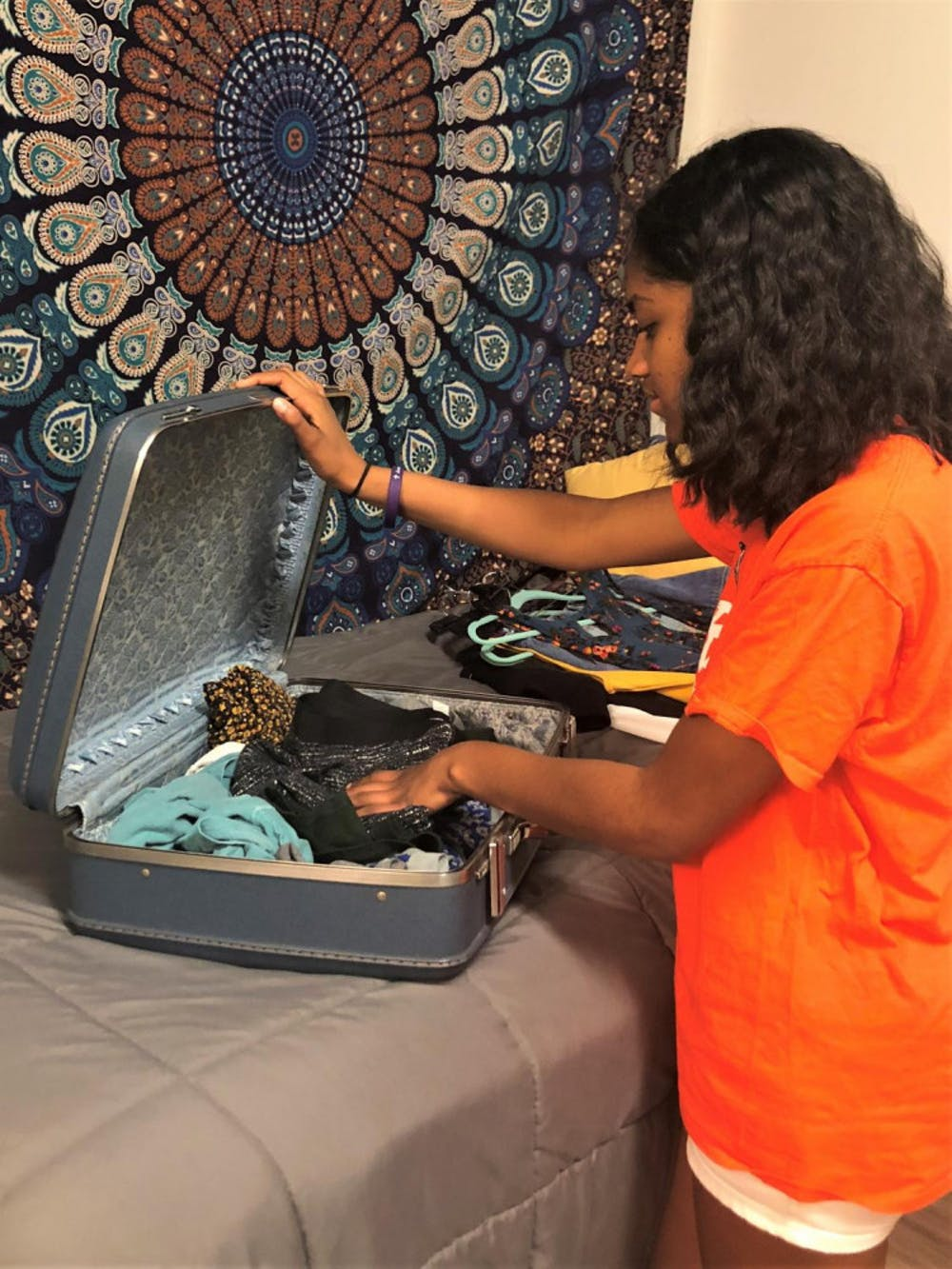 Freshmen Kyra Jackson begins packing her clothes to take home for summer vacation.