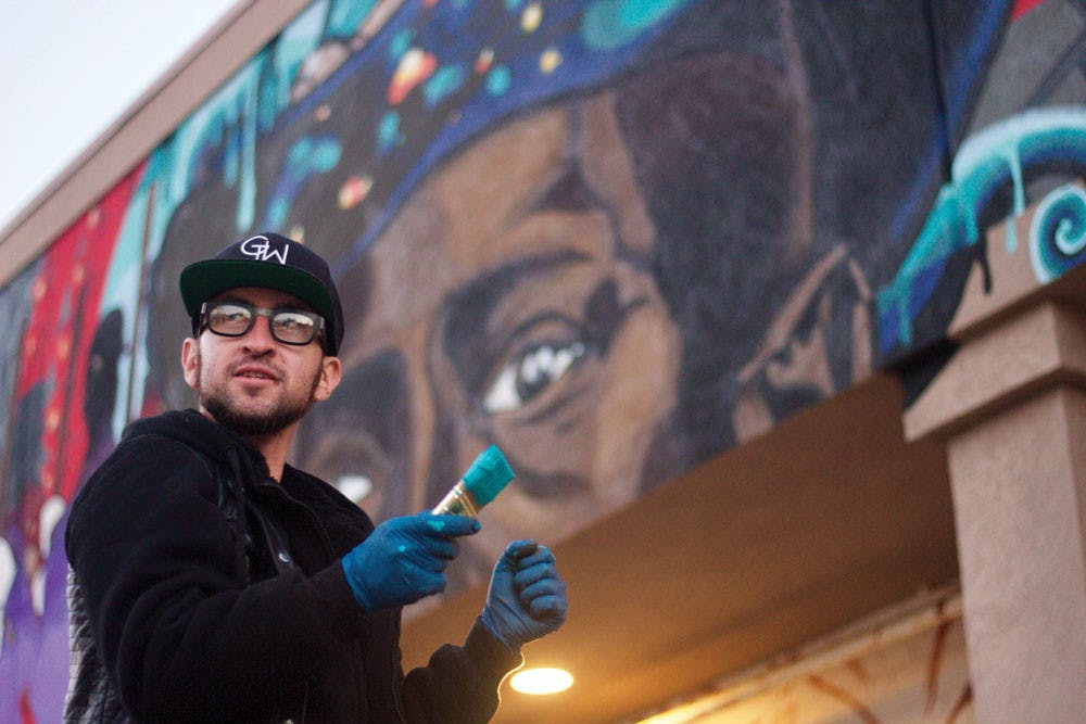"""Artist Joereal Numina paints a mural on the exterior wall of Indigo Salon on Coleman Avenue in 2017. The mural is named """"Cultivating New Tones on the Spectral Stage of History."""""""