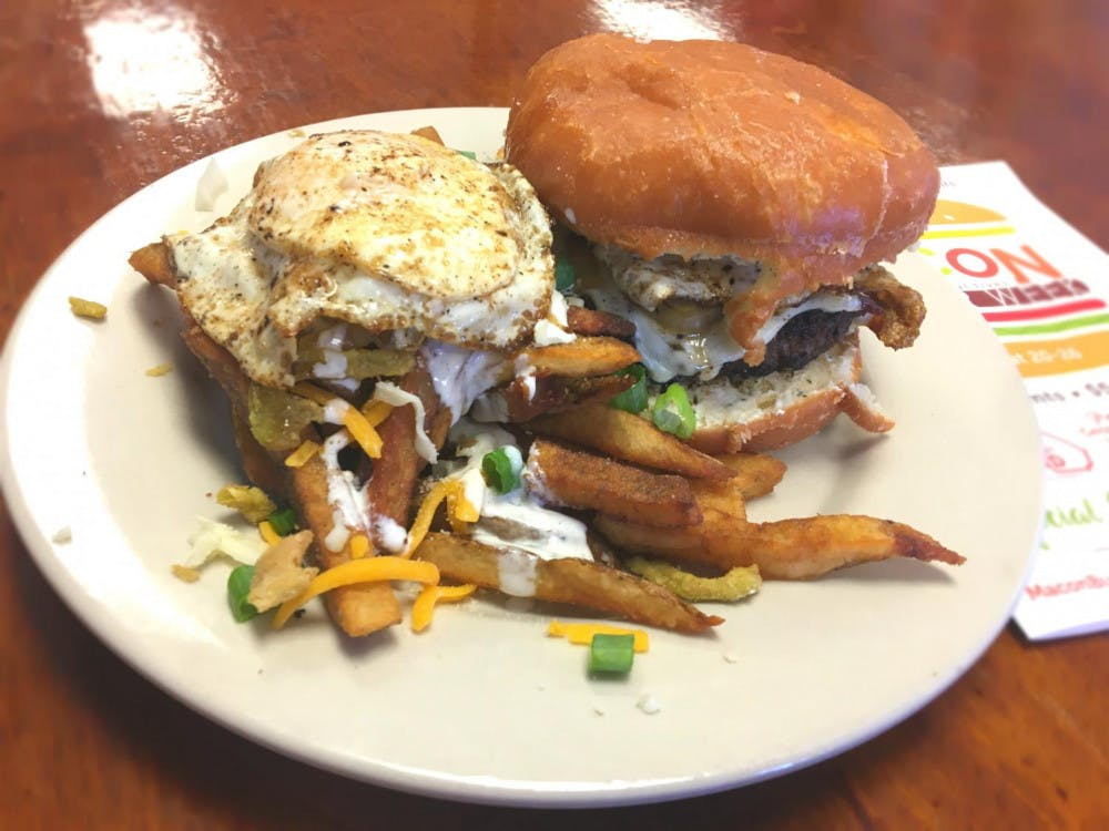 The Donut Burger at Tommy's Bakery and Cafe is served on two donut buns and topped with bacon, cheese, and a fried egg. Photo by Will Darragh