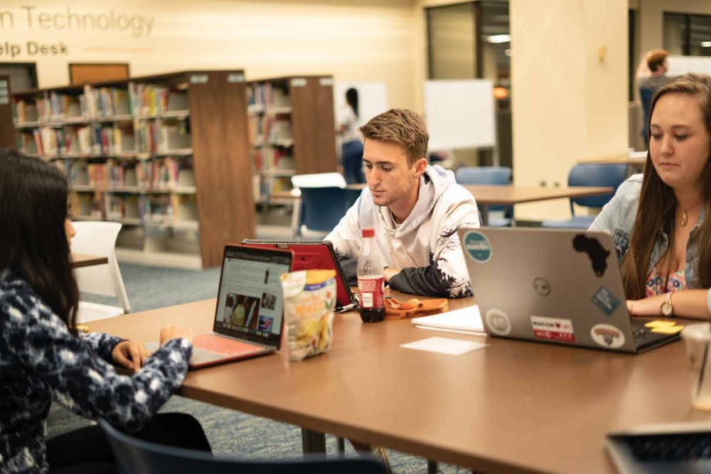 Daniel Wilson and Emily Cadle study in the library.