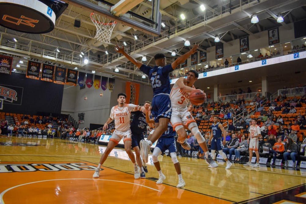 Marcus Cohen (No. 3) struggles to find an open teammate after leaving his feet at the basket.