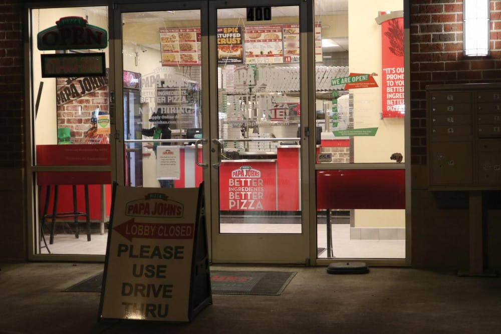 A sign details the restrictions due to COVID-19 at Papa John's Pizza on Mercer University Dr. Jan 27.