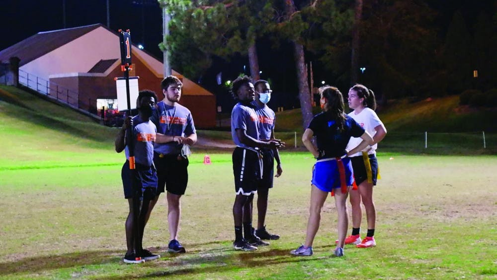 A group of referees speaks with the two teams participating in the Women's Flag Football championship game Oct. 22.